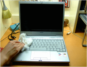 wiping-exterior-of-laptop-with-cloth